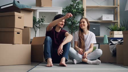 szállás : Bearded guy is giving keys to pretty girlfriend then kissing her sitting on floor in new apartment talking and smiling. Happiness, relationship and relocation concept.