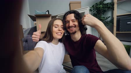 szállás : POV of young husband and wife taking selfie with new flat keys kissing and posing looking at camera showing thumbs-up. Moving to new house and relationship concept.