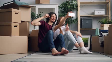 tehcir : Happy couple is taking selfie with house keys using smartphone camera after purchasing new apartment. Young people are posing and kissing with boxes in background.