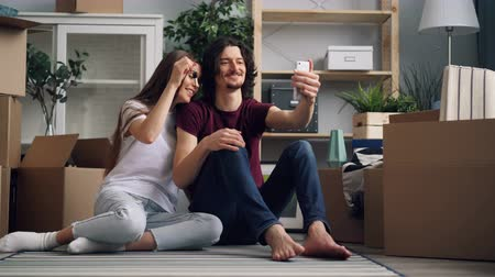 liga : Young man and woman new house owners are making online video call using smartphone in new apartment showing keys talking and showing interior and boxes. Vídeos
