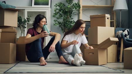 belongings : Happy couple is unpacking things after relocation opening box and looking at photos talking sitting on floor together. Moving to new house and relationship concept.