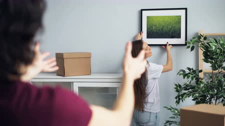 decorating : Husband and wife are picking place for beautiful picture in new house talking and gesturing making rectangle figure with fingers then showing thumbs-up. Stock Footage