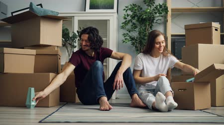 dois objetos : Cheerful girl and guy are unpacking during relocation taking things from box and talking sitting on floor in new house. Household and relationship concept.