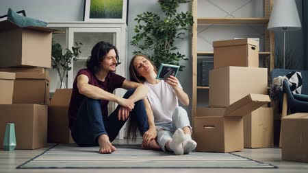 levou : Young woman is taking things from carton box and talking with handsome boyfriend during relocation to new house. Unpacking, housing and relationship concept.