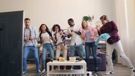 victorious : Playful girls and guys emotional fans are dancing and laughing after victory in sports game on TV at home. Young people are relaxing having fun enjoying time together. Stock Footage