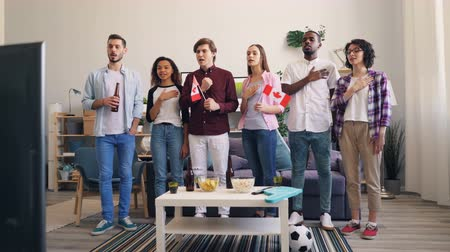 dal : Girls and guys sports fans are singing Canadian anthem waving national flags of Canada watching football on TV at home. People, patriotism and apartment concept. Stock mozgókép