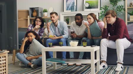 театральный : Friends young people are watching sad movie on TV crying and eating snacks together at home. Pastime, modern television, human emotions and friendship concept. Стоковые видеозаписи