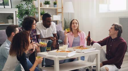 beer house : Happy men and women are talking eating and drinking clanging glasses at house party in apartment. Young people are relaxing at home together celebrating.