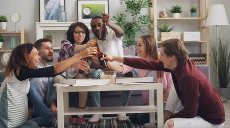 beer house : Female and male students are eating toasting and drinking at enjoyable party in house having fun together. Modern lifestyle, happy millennials and friendship concept.
