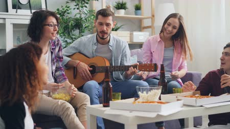 vokal : Happy friends are playing the guitar, singing and laughing at party in apartment. Young people are wearing casual clothing and sitting on sofa and on floor. Stok Video
