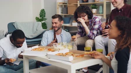 cin cin : Girls and guys are toasting and clinking bottle and glasses eating pizza chatting and laughing at home party together. Celebration and indoor activities concept.