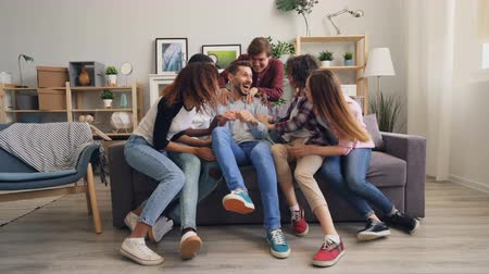 mates : Sad handfsome guy is sitting on sofa alone then joyful friends are running to him hugging and laughing having fun and talking together. Friendship and house concept. Stock Footage