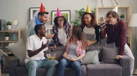 assobio : Laughing friends in party hats are congratulating happy girl on birthday feeding her crisps and singing having fun with snacks and alcohol. People and holidays concept.
