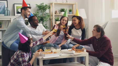 beer house : Happy young people wearing party hats are celebrating birthday eating and drinking at home together clinking bottles toasting. Celebration and youth concept. Stock Footage