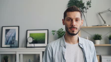 ombros : Slow motion portrait of handsome young man looking at camera with straight face standing at home alone. Millennials, attractive people and house concept.