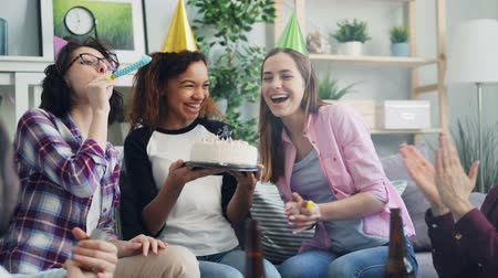 assobio : Slow motion of happy African American woman blowing candles on birthday cake celebrating with friends laughing having fun. Men and women blowing party whistles and throwing confetti. Stock Footage
