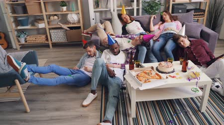 cansado : Drunk girls and guys friends are sleeping on floor and sofa wearing bright colorful hats after joyful party in apartment. Modern lifestyle and holidays concept.