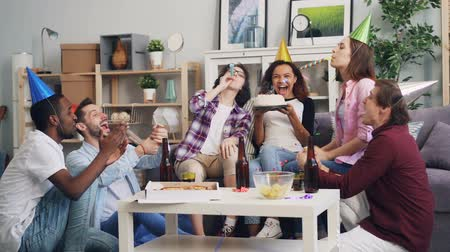 enjoyable : Slow motion of joyful youth celebrating birthday with cake, colorful confetti and party whistles. African American girl is blowing candles, friends are congratulating. Stock Footage