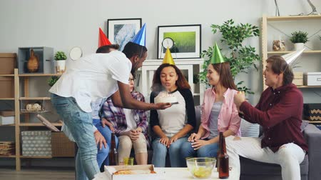 笛 : Birthday girl pretty African American woman is blowing candles on cake when happy friends are throwing confetti clapping hands and blowing party whistle