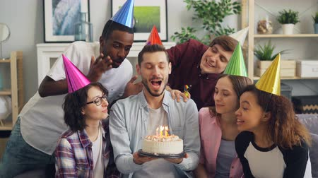 fischietto : Happy guy singing with friends wearing party hats then making wish and blowing candles on birthday cake while men and women clapping hands and talking