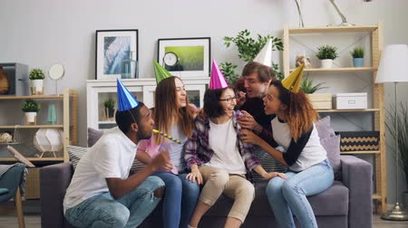 apito : Friends young men and women are congratulating unhappy girl on birthday making surprise singing song bringing cake with candles. Party and friendship concept. Stock Footage