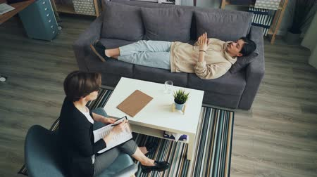 sharing : High angle view of teenage boy talking to psychologist discussing troubles lying on couch in office speaking and gesturing. Female doctor is listening. Stock Footage