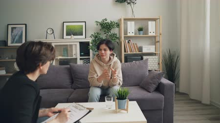 встреча : Zoom in of emotional teenage kid discussing life talking to psychologyst sitting on sofa in office and gesturing. Feelings, emotions and psychological help concept. Стоковые видеозаписи