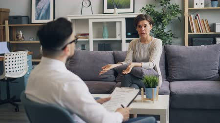 psychiatrist : Angry woman client is expressing negative emotions during counselling session with psychologist in modern office. Negativity, unhappy people and anger concept. Stock Footage