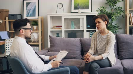 counselling : Therapist handsome man is talking to female patient in office making notes asking questions during individual counselling in office. People and psychology concept.