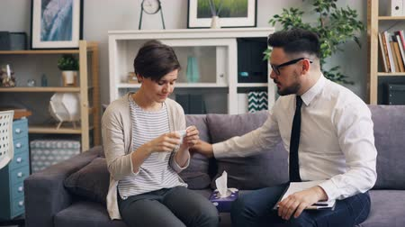 miserável : Helpful male therapist is comforting stressed woman crying in office giving her paper tissue giving advice sitting on couch together having conversation discussing problem.