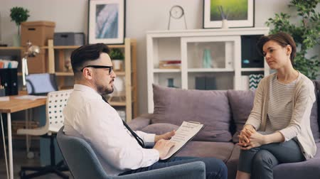 counselling : Professional psychologist bearded young man is discussing problems with depressed woman in office. Specialist is asking questions sitting in armchair holding paper.