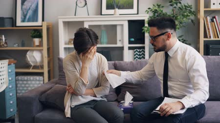 traumatic : Caring psychologist handsome bearded guy is helping crying woman depressed patient giving her paper tissue touching shoulder and talking comforting her. Stock Footage