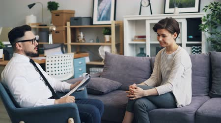 counselling : Successful psychologist handsome guy is giving advice to sad young woman talking in office during private consultation. Advice, counselling and youth concept. Stock Footage