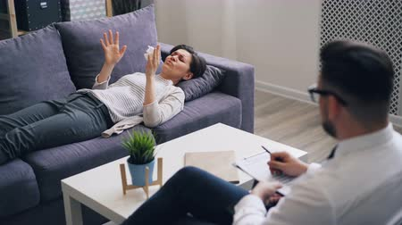 psychiatrist : Upset girl in casual clothing is discussing emotions with psychologist lying on couch in office talking and gesturing. Women, healthcare and psychology concept.