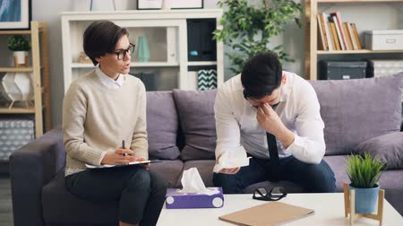 sharing : Desperate guy is crying in therapists office talking about troubles in business touching face with paper tissue telling sad story. Specialist is listening sitting beside.