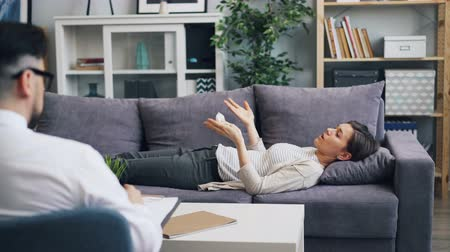 counselling : Young woman is speaking with male psychologist lying on sofa in office talking and gesturing expressing emotions. People and psychological help concept.