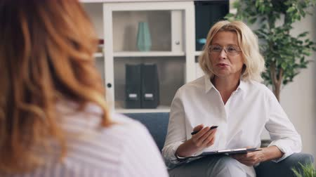 professionalism : Positive therapist good-looking blond woman is giving advice to obese young lady during consultation in office. Occupation, people and psychology concept.