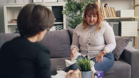 psiquiatra : Depressed young obese woman with red hair is crying talking to psychotherapist in office while doctor is comforting her giving advice. Negative emotions and people concept.