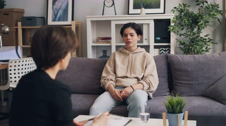 counselling : Teenage boy in trendy clothing is listening to female psychologist sitting in office on couch during consultation. Childhood, psychotherapy and people concept.
