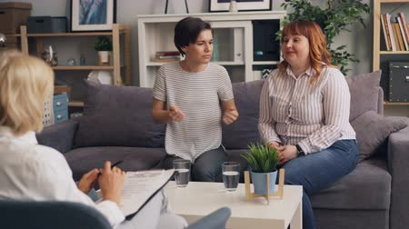 консультация : Young women friends are talking to psychologist discussing problems in relationship sitting on couch together speaking and gesturing. People and psychology concept.
