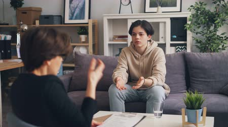counselling : Stressed boy unhappy teenager is speaking with young woman psychologist in office discussing behavior problems. Psychotherapy, people and youth concept.
