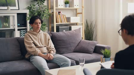 personalidade : Unhappy young boy in casual clothing is opening up to female therapist in juvenile psychology center. Troubled youth, communication and mental health concept. Stock Footage