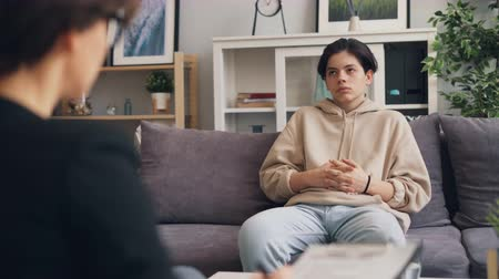 counselling : Depressed teen is having serious conversation with female psychotherapist in modern office sitting on couch and speaking. Depression, youth and psychological help concept.