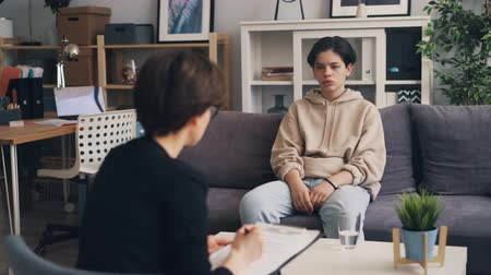 counselling : Sad lonely teenager is opening up to professional therapist in psychologists office in clinic. Upset boy is sitting on couch gesturing and telling story.