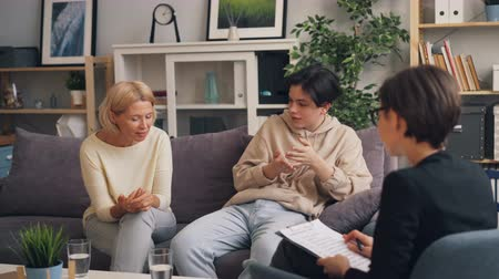 подростковый возраст : Woman and teenager are discussing mother son relationship with female therapist sitting on couch together and talking. Family problems and professional help concept.