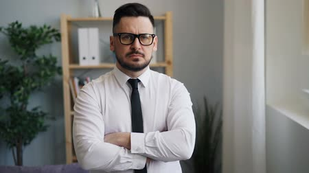 строгий : Slow moton portrait of serious businessman bearded middle-aged man with dark hair and trimmed beard standing in office with crossed arms looking at camera. Стоковые видеозаписи