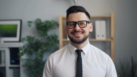 dişlek : Slow motion portrait of bearded man successful businessman looking at camera and smiling in office. Business people, handsome guys and workplace concept. Stok Video