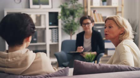 tense : Teenager is fighting with mature mother during consultation with psychologist sitting on couch and talking expressing negative emotions. Youth and parents concept. Stock Footage