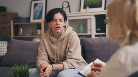értékelés : Nervous teenager good-looking boy in trendy clothing is communicating with female psychoanalyst during personal session in clinic. Youth and emotions concept.