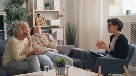 rude : Mature lady and teenage son are discussing family problems with psychologist sitting on couch and talking. Parenting, psychology and unhappy teenagers concept.